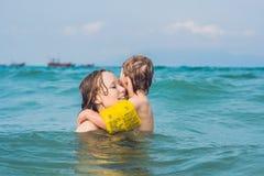 Молодое заплывание матери и играть с мальчиком мальчика в дне воды моря или океана солнечном внешнем на естественной предпосылке, Стоковое Изображение RF