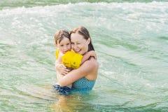 Молодое заплывание матери и играть с мальчиком мальчика в дне воды моря или океана солнечном внешнем на естественной предпосылке, Стоковые Изображения