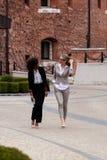 2 молодое и привлекательная коммерсантка идя и имея переговор Одна женщина черна с вьющиеся волосы Стоковое Изображение RF