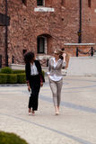 2 молодое и привлекательная коммерсантка идя и имея переговор Одна женщина черна с вьющиеся волосы Стоковое Фото