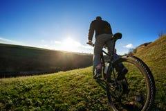 Молодое катание велосипедиста на красивом следе луга на солнечный день Стоковая Фотография