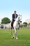 Молодое катание groom на белой лошади стоковые изображения rf