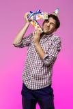 Молодое красивое избежание человека от коробки дня рождения над фиолетовой предпосылкой стоковое изображение rf