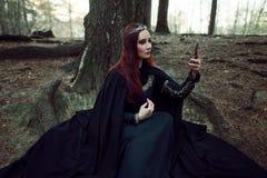 Молодое красивое и загадочное изображение женщины эльфа или ведьмы леса, смотря в зеркале Стоковые Изображения