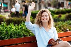 Молодое красивое приветствие девушки, усаживание на стенде в парке города Стоковое Фото