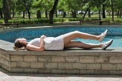 Молодое красивое платье девушки вкратце белое лежит около фонтана Стоковые Изображения RF