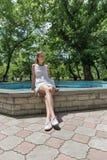Молодое красивое платье девушки вкратце белое сидит около фонтана Стоковые Изображения RF