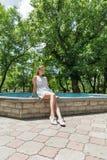 Молодое красивое платье девушки вкратце белое сидит около фонтана Стоковая Фотография