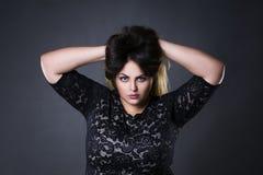 Молодое красивое плюс модель в черных dres шнурка, портрет размера женщины xxl на серой предпосылке студии Стоковое Изображение RF