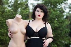 Молодое красивое плюс modelt размера в черном бюстгальтере держа манекен Стоковые Изображения