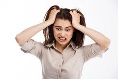 Молодое красивое сердитое шальное businessgirl брюнет схватывая ее голову и кричащий рассматривать прочь белая предпосылка Стоковое фото RF