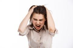 Молодое красивое сердитое шальное businessgirl брюнет схватывая ее голову и кричащий рассматривать вниз белая предпосылка Стоковые Изображения RF