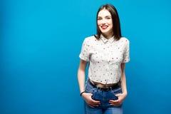 Молодое милое smilig женщины на голубой предпосылке Стоковые Изображения