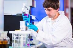 Молодое мужское научное исследование приведения в исполнение исследователя в лаборатории Стоковое Изображение