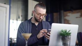 Молодое мужское усаживание в кафе с smartphone Молодой мужчина битника в стеклах сидя в кафе с компьтер-книжкой и используя телеф сток-видео