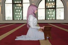 Молодое мусульманское koran чтения девушки Стоковая Фотография