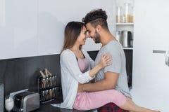 Молодое объятие пар в кухне, испанском человеке и азиатском объятии женщины Стоковое Изображение RF