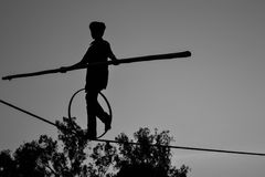 Молодое опасное положение идя, Slacklining мальчика, Funambulism, балансировать веревочки стоковое фото