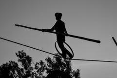Молодое опасное положение идя, Slacklining мальчика, Funambulism, балансировать веревочки стоковое фото rf
