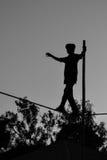 Молодое опасное положение идя, Slacklining мальчика, Funambulism, балансировать веревочки стоковые фото