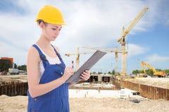 Молодое привлекательное сочинительство построителя женщины что-то в доске сзажимом для бумаги Стоковое Изображение