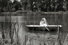 Молодое плавание пар свадьбы на шлюпке Стоковая Фотография RF