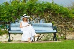 Молодое сексуальное чтение женщины в пляже Стоковая Фотография RF
