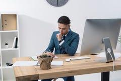 Молодое сочинительство бизнесмена в тетради пока работающ на таблице с настольным компьютером Стоковая Фотография