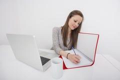 Молодое сочинительство коммерсантки в книге на столе офиса Стоковая Фотография RF