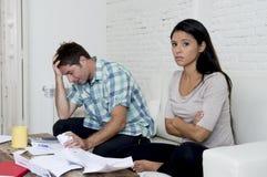 Молодое унылое кресло живущей комнаты пар дома высчитывая ежемесячные расходы потревожилось в стрессе Стоковые Фото