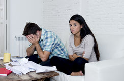 Молодое унылое кресло живущей комнаты пар дома высчитывая ежемесячные расходы потревожилось в стрессе Стоковое фото RF