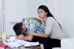 Молодое унылое кресло живущей комнаты пар дома высчитывая ежемесячные расходы потревожилось в стрессе Стоковое Изображение