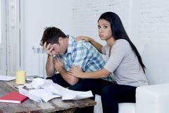 Молодое унылое кресло живущей комнаты пар дома высчитывая ежемесячные расходы потревожилось в стрессе Стоковая Фотография