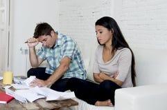 Молодое унылое кресло живущей комнаты пар дома высчитывая ежемесячные расходы потревожилось в стрессе Стоковые Изображения