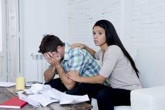 Молодое унылое кресло живущей комнаты пар дома высчитывая ежемесячные расходы потревожилось в стрессе Стоковое Фото
