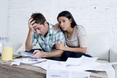 Молодое унылое кресло живущей комнаты пар дома высчитывая ежемесячные расходы потревожилось в стрессе Стоковые Изображения RF