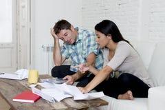 Молодое унылое кресло живущей комнаты пар дома высчитывая ежемесячные расходы потревожилось в стрессе Стоковое Изображение RF