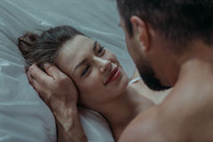 Молодое любящее объятие пар в кровати Стоковое фото RF