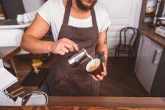 Молодое barista делая latte в столовой стоковая фотография