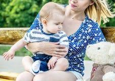 Молодое mather при маленький сын сидя на ее коленях с медведем игрушки на стенде в парке стоковые фото