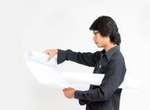 Молодой азиатский архитектор человека смотря к плану Стоковые Изображения