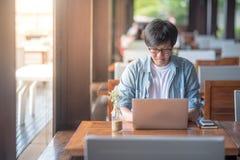 Молодой азиатский бизнесмен работая с компьтер-книжкой в кафе стоковое фото
