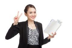 Молодой азиатский знак Виктора выставки бизнес-леди с книгой Стоковое Изображение RF