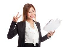 Молодой азиатский знак Виктора выставки бизнес-леди с книгой Стоковая Фотография