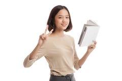 Молодой азиатский знак Виктора выставки бизнес-леди с книгой Стоковые Фотографии RF
