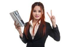 Молодой азиатский знак Виктора выставки бизнес-леди с книгой Стоковые Изображения RF