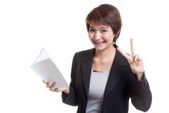 Молодой азиатский знак Виктора выставки бизнес-леди с книгой Стоковые Изображения