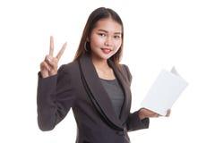 Молодой азиатский знак Виктора выставки бизнес-леди с книгой Стоковые Фото