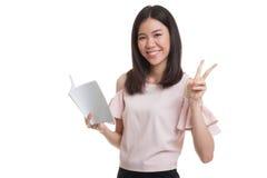 Молодой азиатский знак Виктора выставки бизнес-леди с книгой Стоковое Фото