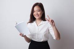 Молодой азиатский знак Виктора выставки женщины с книгой Стоковые Фотографии RF